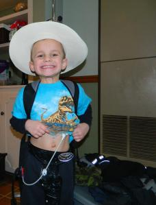 Playing cowboy with his feeding book bag on